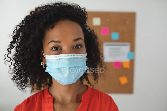 Ritratto di donna di razza mista business creativo in piedi in un ufficio con indosso maschera. Salute e igiene sul luogo di lavoro durante la pandemia di Coronavirus Covid 19. — Foto stock