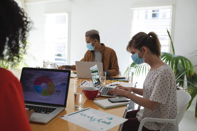 Multi ethnic group of male and female creative business colleagues working in modern office wearing face masks. Health and hygiene in the workplace during Coronavirus Covid 19 pandemic. — Stock Photo