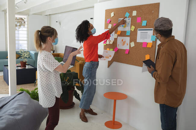 Multi ethnic group of male and female business creatives stand brainstorming in modern office wearing face masks. Health and hygiene in the workplace during Coronavirus Covid 19 pandemic. — Stock Photo