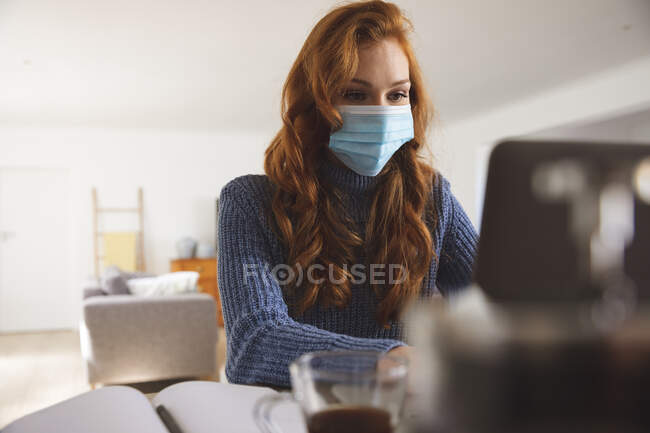 Caucasian woman spending time at home, in the kitchen, working from home, using her laptop,  wearing a face mask. Social distancing during Covid 19 Coronavirus quarantine lockdown. — Stock Photo