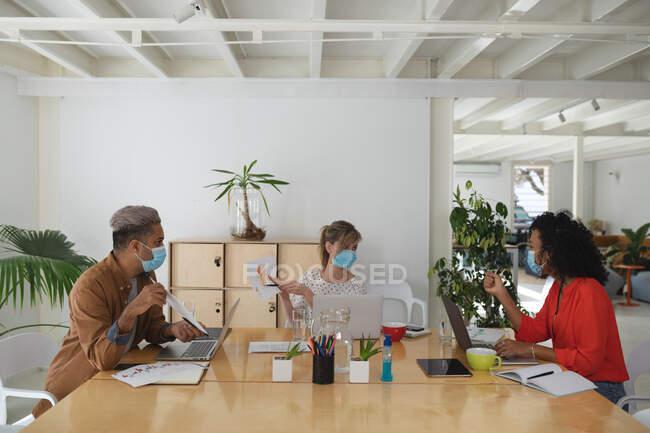 Gruppo multietnico di uomini e donne creativi d'affari nell'incontro indossando maschere facciali che discutono documenti. Salute e igiene sul luogo di lavoro durante la pandemia di Coronavirus Covid 19. — Foto stock