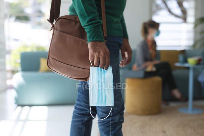 Metà sezione di uomini d'affari creativo in piedi in ufficio foyer in possesso di valigetta e maschera. Salute e igiene sul luogo di lavoro durante la pandemia di Coronavirus Covid 19. — Foto stock