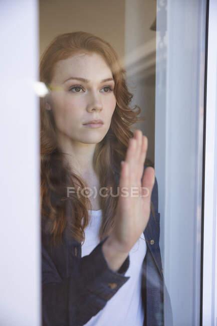 Une jolie femme caucasienne rousse passe du temps à la maison, dans le salon, regardant par la fenêtre. Distance sociale pendant le confinement en quarantaine du coronavirus Covid 19. — Photo de stock