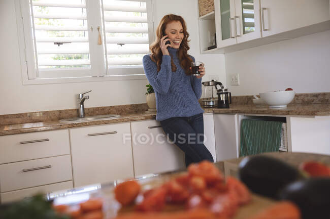 Caucasian woman spending time at home, in kitchen, talking on the phone, smiling and drinking from a glass. Social distancing during Covid 19 Coronavirus quarantine lockdown. — Stock Photo