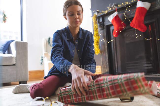 Donna caucasica trascorrere del tempo a casa a Natale, seduto sul pavimento vicino al camino in soggiorno, avvolgente presente nella carta. Distanza sociale durante il blocco di quarantena Covid 19 Coronavirus. — Foto stock