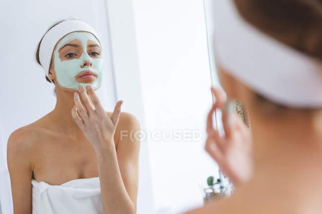 Kaukasische Frau, die Zeit zu Hause verbringt, im Badezimmer steht und in den Spiegel schaut, der Gesichtsmaske aufsetzt. Soziale Distanzierung während Covid 19 Coronavirus Quarantäne Lockdown. — Stockfoto