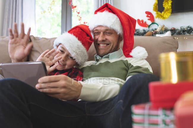 Кавказький чоловік з сином на Різдво, одягнений у Санта-Капелюхи сидячи на дивані у вітальні, використовуючи цифрову табличку, махаючи руками. Соціальна дистанція в Ковиді 19 Коронавірус карантин. — стокове фото