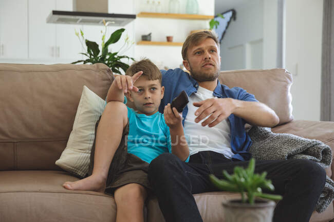 Caucasian man at home with his son together, sitting on sofa in living room, watching TV. Social distancing during Covid 19 Coronavirus quarantine lockdown. — Stock Photo