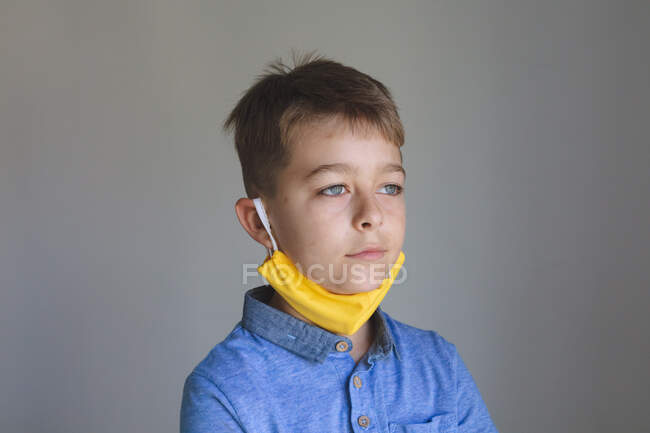 Side view of Caucasian boy spending time at home, wearing yellow face mask looking at camera on grey background. Social distancing during Covid 19 Coronavirus quarantine lockdown. — Stock Photo