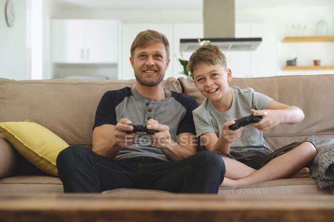 Caucasian man at home with his son together, sitting on sofa in living room, playing video games, smiling. Social distancing during Covid 19 Coronavirus quarantine lockdown. — Stock Photo