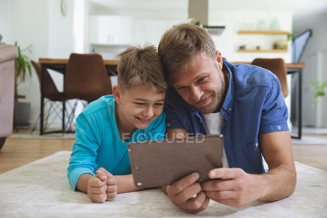 Kaukasischer Mann zu Hause mit seinem Sohn zusammen, auf Teppich im Wohnzimmer liegend, mit digitalem Tablet, lächelnd. Soziale Distanzierung während Covid 19 Coronavirus Quarantäne Lockdown. — Stockfoto