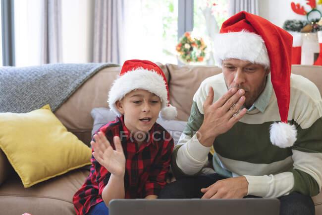 Homme caucasien à la maison avec son fils à Noël, portant des chapeaux de Père Noël assis dans le salon en utilisant un ordinateur portable pour un appel vidéo. Distance sociale pendant le confinement en quarantaine du coronavirus Covid 19. — Photo de stock