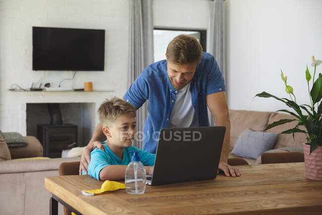 Kaukasischer Mann zu Hause mit seinem Sohn zusammen, Junge am Tisch, Laptop, Vater neben ihm. Soziale Distanzierung während Covid 19 Coronavirus Quarantäne Lockdown. — Stockfoto