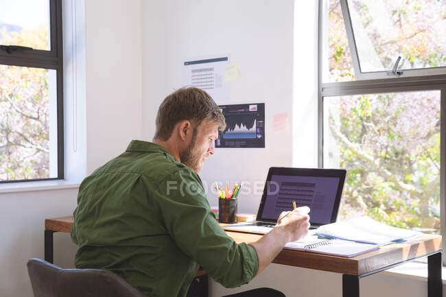 Белый мужчина проводит время дома, работает из дома, использует ноутбук, делает заметки. Социальное дистанцирование во время изоляции коронавируса Covid 19. — стоковое фото