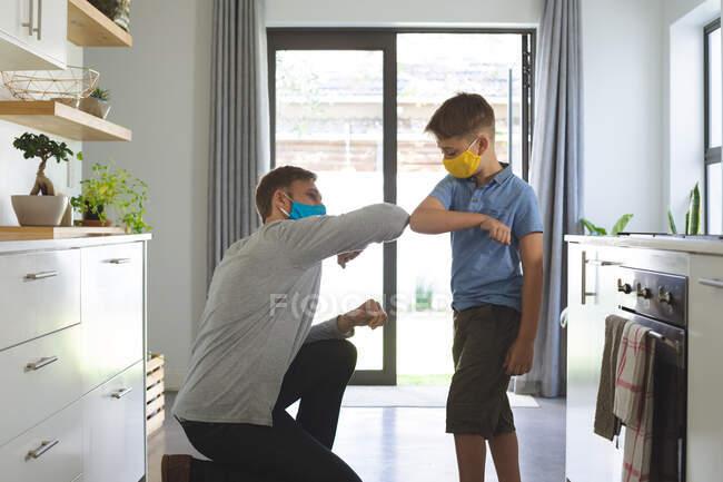 Kaukasischer Mann zu Hause bei seinem Sohn, in der Küche, Gesichtsmasken tragend, mit berührenden Ellbogen grüßend. Soziale Distanzierung während Covid 19 Coronavirus Quarantäne Lockdown. — Stockfoto