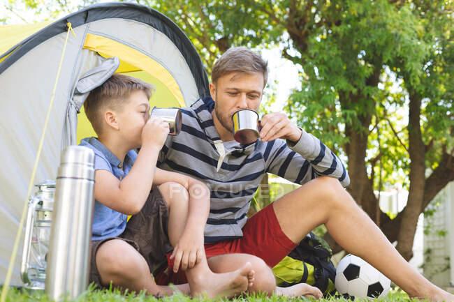 Hombre caucásico pasando tiempo con su hijo juntos, acampando en el jardín, sentado en la tienda, bebiendo té. Distanciamiento social durante el bloqueo de cuarentena del Coronavirus Covid 19. - foto de stock