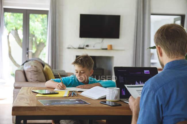 Kaukasischer Mann zu Hause mit seinem Sohn zusammen, am Tisch in der Küche, Vater arbeitet mit Laptop, Junge macht Hausaufgaben. Soziale Distanzierung während Covid 19 Coronavirus Quarantäne Lockdown. — Stockfoto