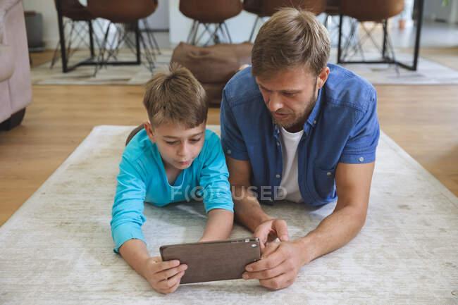 Kaukasischer Mann zu Hause mit seinem Sohn zusammen, auf Teppich im Wohnzimmer liegend, mit digitalem Tablet. Soziale Distanzierung während Covid 19 Coronavirus Quarantäne Lockdown. — Stockfoto