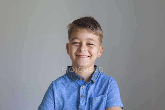 Portrait d'un garçon caucasien heureux passant du temps à la maison, souriant et regardant la caméra sur fond gris. Distance sociale pendant le confinement en quarantaine du coronavirus Covid 19. — Photo de stock