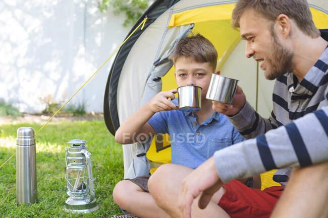Hombre caucásico pasando tiempo con su hijo juntos, acampando en el jardín, sentado al lado de la tienda de campaña bebiendo té, sonriendo. Distanciamiento social durante el bloqueo de cuarentena del Coronavirus Covid 19. - foto de stock