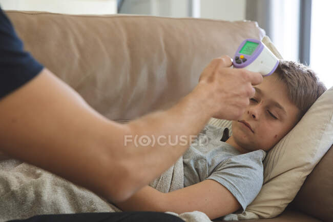 Caucasian man at home with his son together, boy lying on sofa in living room, father measuring temperature with digital thermometer. Social distancing during Covid 19 Coronavirus quarantine lockdown. — Foto stock