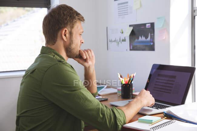 Hombre caucásico pasar tiempo en casa, trabajando desde casa, utilizando el ordenador portátil. Distanciamiento social durante el bloqueo de cuarentena del Coronavirus Covid 19. - foto de stock