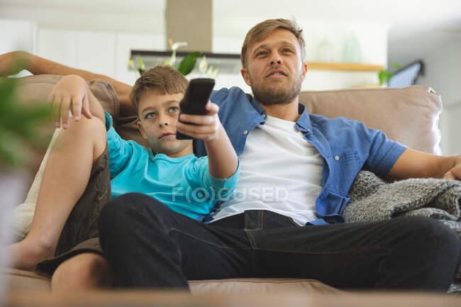 Kaukasischer Mann zu Hause mit seinem Sohn zusammen, auf dem Sofa im Wohnzimmer sitzend, vor dem Fernseher. Soziale Distanzierung während Covid 19 Coronavirus Quarantäne Lockdown. — Stockfoto