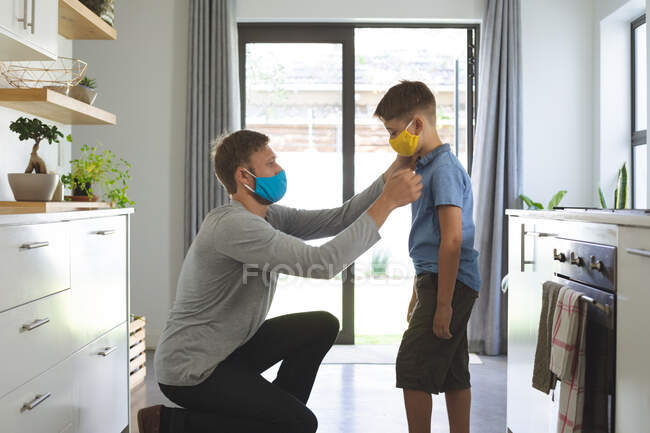 Caucasian man at home with his son in kitchen, wearing face masks, man helping his son. Social distancing during Covid 19 Coronavirus quarantine lockdown. — Stock Photo