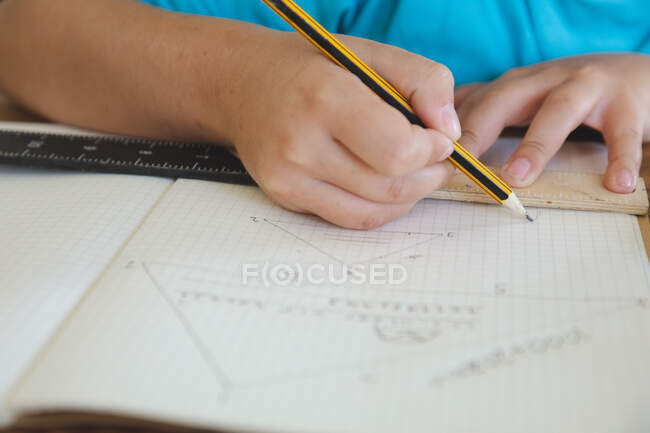 Mid section of boy spending time at home, home schooling, doing mathematics homework. Social distancing during Covid 19 Coronavirus quarantine lockdown. — Stock Photo