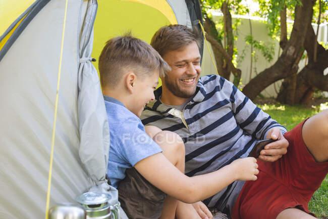 Hombre caucásico pasar tiempo con su hijo juntos, acampar en el jardín, acostado en la tienda de campaña con el teléfono inteligente, sonriendo. Distanciamiento social durante el bloqueo de cuarentena del Coronavirus Covid 19. - foto de stock
