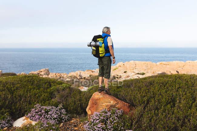 Homme âgé passer du temps dans la nature, marcher dans les montagnes, profiter de la vue. mode de vie sain activité de retraite. — Photo de stock