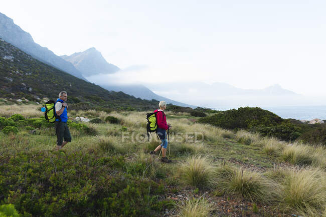 Senior couple spending time in nature together, walking in the mountains. healthy lifestyle retirement activity. — Stock Photo