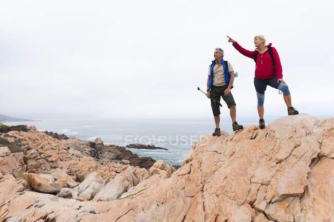 Старшая пара проводит время на природе вместе, гуляя в горах, женщина указывает вверх. активный уход на пенсию. — стоковое фото