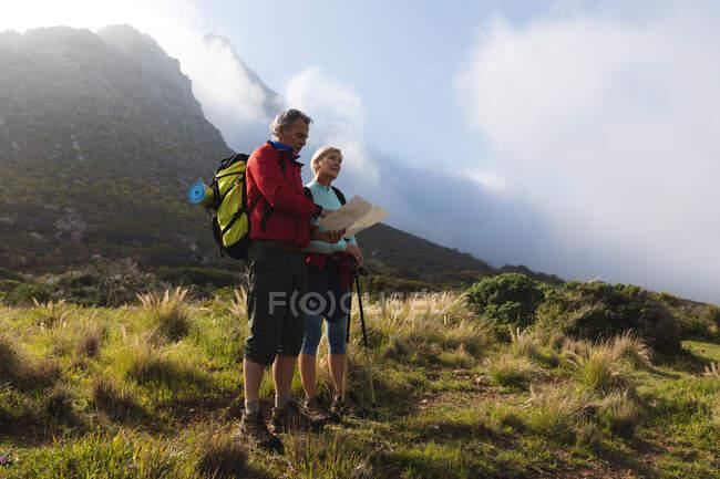 Старшая пара проводит время на природе вместе, гуляет по горам, смотрит на карту. активный уход на пенсию. — стоковое фото