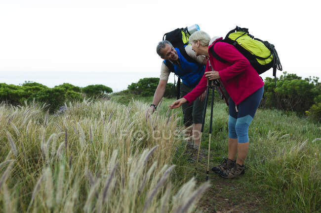 Senior couple spending time in nature together, walking in mountains, touching grass and smiling. healthy lifestyle retirement activity. — Stock Photo