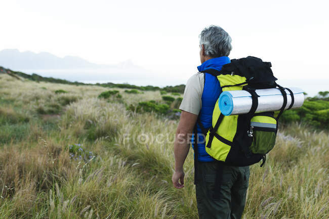 Старший мужчина проводит время на природе вместе, гуляя в горах, оглядываясь вокруг. активный уход на пенсию. — стоковое фото