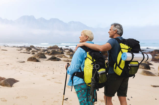 Coppia anziana trascorrere del tempo in natura insieme, passeggiando sulla spiaggia, l'uomo sta abbracciando donna. stile di vita sano attività pensionistica. — Foto stock