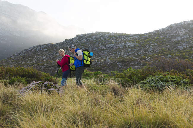 Senior couple spending time in nature together, walking in the mountains, talking. healthy lifestyle retirement activity. — Stock Photo