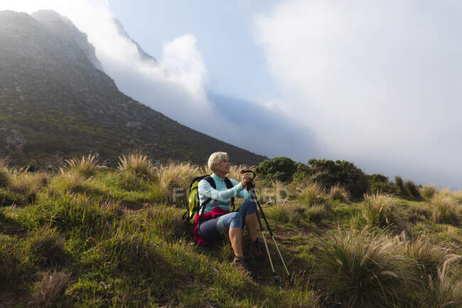 Senior woman spending time in nature, walking in the mountains, sitting on grass, enjoying the view. healthy lifestyle retirement activity. — Stock Photo