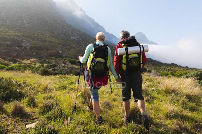 Coppia anziana trascorrere del tempo nella natura insieme, passeggiando in montagna, tenendosi per mano. stile di vita sano attività pensionistica. — Foto stock