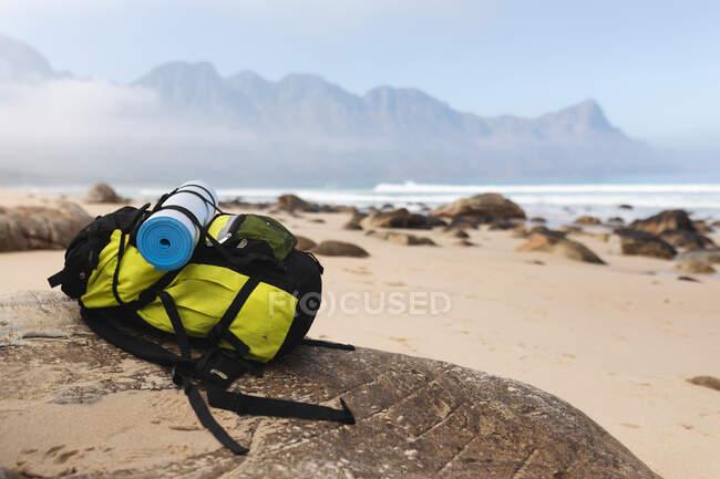 Sac à dos couché sur un rocher sur une plage au bord d'une mer calme. — Photo de stock