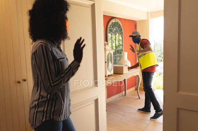 Entrega homem usando máscara facial entregando pacote para mulher usando máscara facial em casa. distanciamento social durante o bloqueio de quarentena do coronavírus covid 19 — Fotografia de Stock