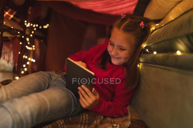 Ragazza caucasica sorridente e utilizzando tablet computer, seduto in fortezza coperta con luci fatate. isolamento durante il coronavirus covid 19 isolamento di quarantena. — Foto stock