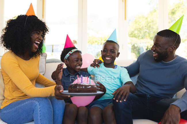 African american family wearing party hats with cake celebrating birthday sitting on the couch in the living room at home. social distancing during covid 19 coronavirus quarantine lockdown. — Stock Photo
