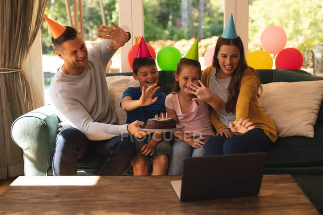 Caucasian family making a video call using a laptop at home together while celebrating a birthday wearing party hats. quality family time together during coronavirus covid 19 quarantine lockdown. — Stock Photo
