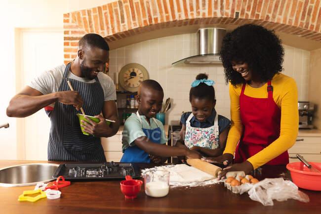 Famiglia afroamericana che indossa grembiuli che cuociono insieme in cucina a casa. Natale festa tradizione celebrazione concetto — Foto stock