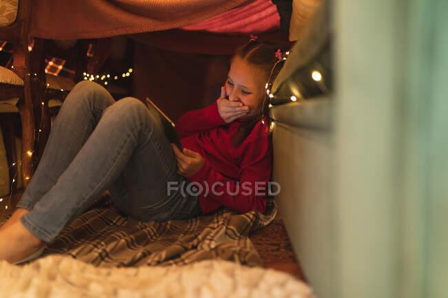 Kaukasisches Mädchen, lachend und mit Tablet-Computer, in einer Deckenfestung mit Lichterketten sitzend. Selbstisolation während Coronavirus covid 19 Quarantäne Lockdown. — Stockfoto