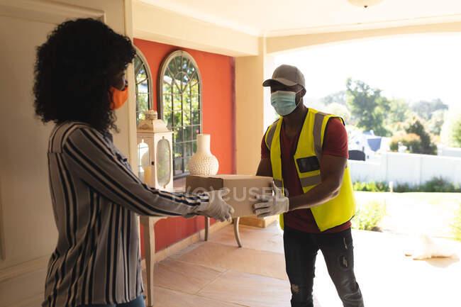 Доставщик в маске доставляет посылку женщине в маске для лица дома. социальное дистанцирование во время блокады 19 коронавируса — стоковое фото