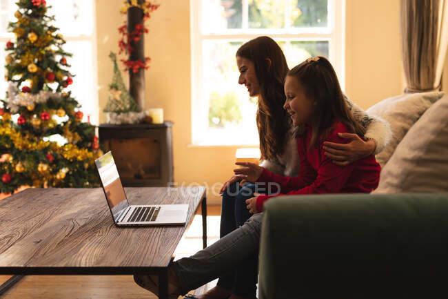 Femme caucasienne et sa fille assis sur le canapé et souriant, faire un appel vidéo à l'aide d'un ordinateur portable à la période de Noël. isolement volontaire pendant le confinement en quarantaine du coronavirus covid 19. — Photo de stock