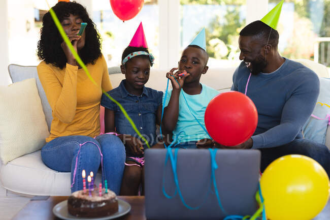 African american family wearing party hats celebrating birthday and blowing party blowers while sitting on the couch in the living room at home. social distancing during covid 19 coronavirus quarantine lockdown. — Stock Photo